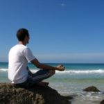Picture of a man meditating on a beach
